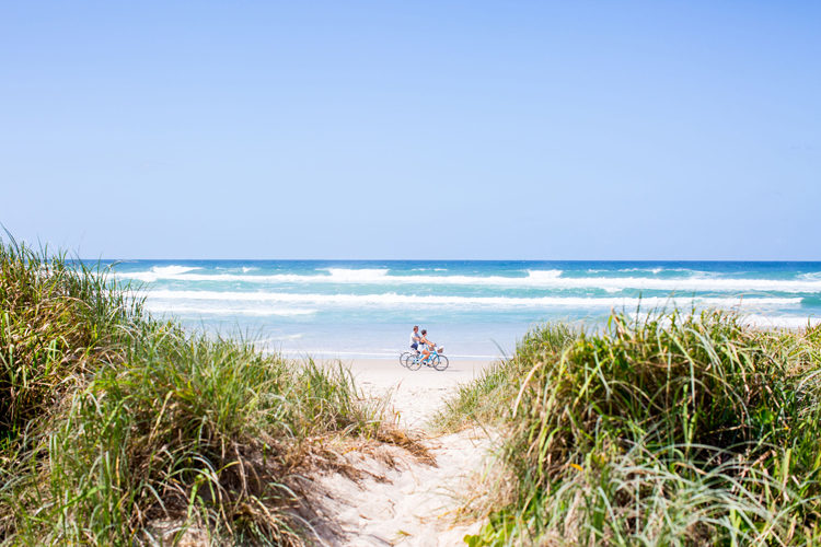 couple riding along the beach infront of Halcyon House